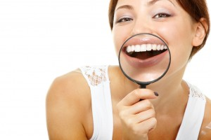 funny woman smiling and show teeth through a magnifying glass ov
